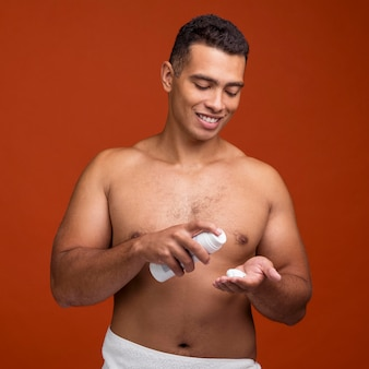 Front view of smiley shirtless man using shaving foam