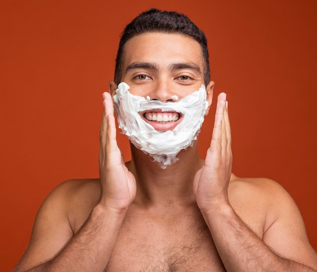 Front view of smiley shirtless man with shaving foam on his face