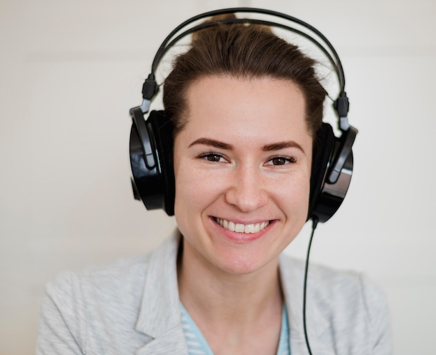 Front view of smiley teacher wearing headphones for online class