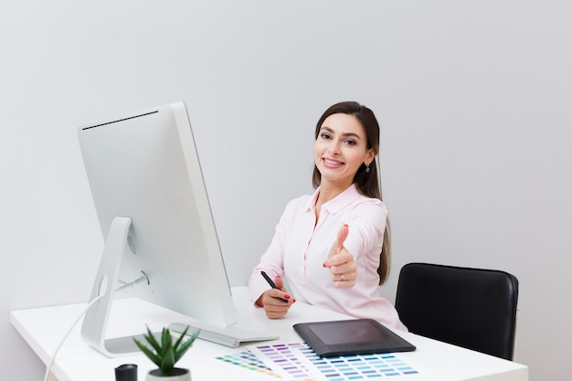 Front view of smiley woman at desk giving thumbs up