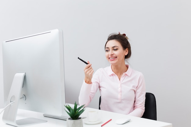 Front view of smiley woman at desk pointing pen at the computer