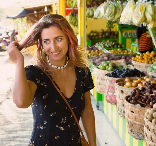 Vista frontale della donna sorridente al mercato degli agricoltori
