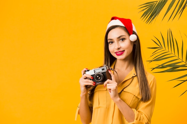 Front view of smiley woman holding camera while wearing santa hat with copy space