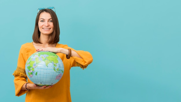 Front view of smiley woman holding earth globe with copy space