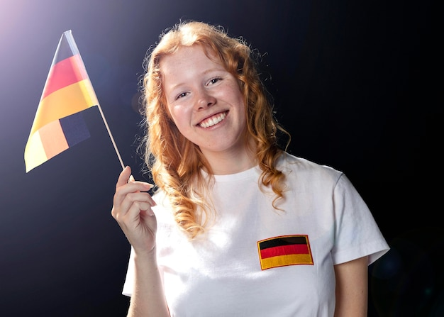 Front view of smiley woman holding german flag