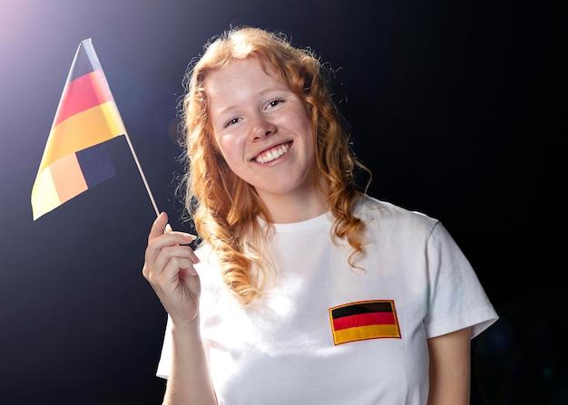 Vista frontale della donna sorridente che tiene bandiera tedesca