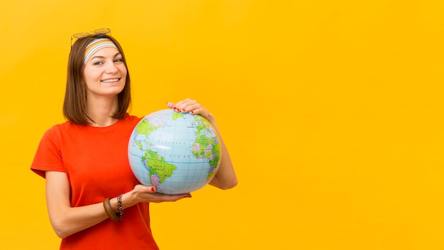Front view of smiley woman holding globe with copy space