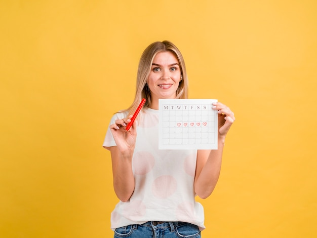 Front view smiley woman holding period calendar