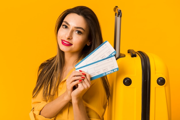 Front view of smiley woman holding plane tickets