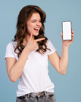 Front view of smiley woman holding and pointing at smartphone