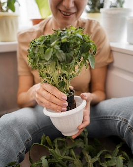 Vista frontale della donna sorridente che tiene il vaso della pianta
