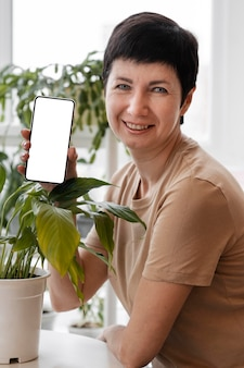 Front view of smiley woman holding smartphone next to indoor plants