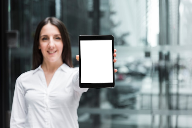 Front view smiley woman holding up a tablet