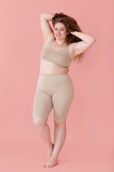 Front view of smiley woman posing while wearing a body shaper