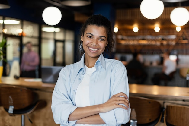 Front view of smiley woman posing with crossed arms in the workplace