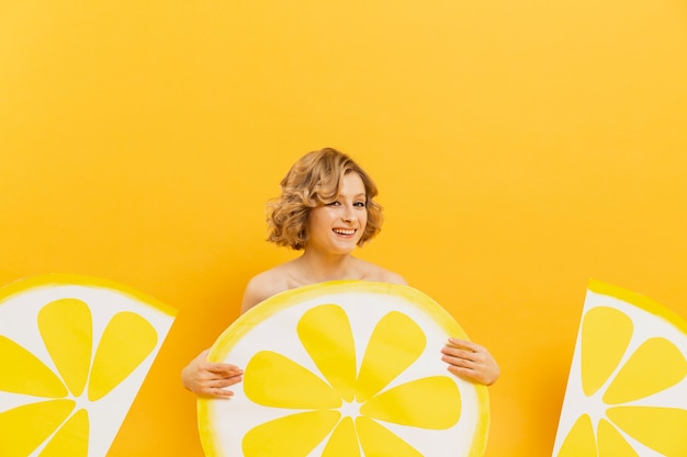 Front view of smiley woman posing with lemon slices decor