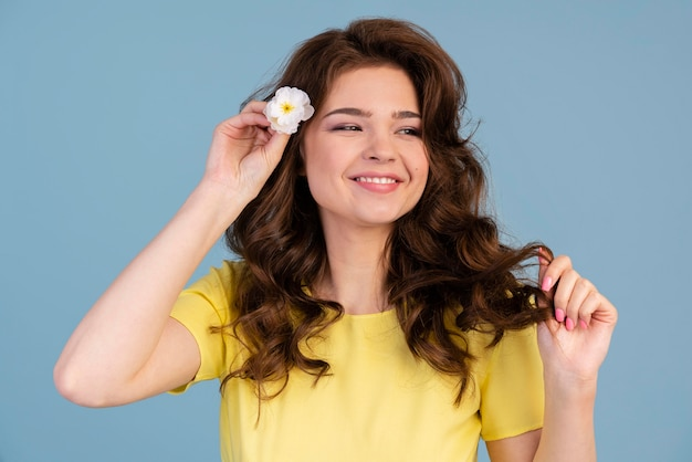Front view of smiley woman putting a flower in her hair
