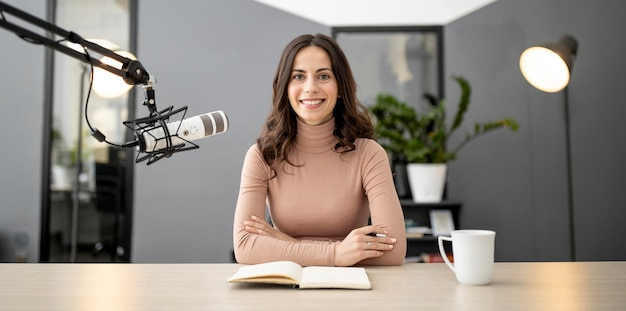 Front view of smiley woman on the radio with microphone and notebook