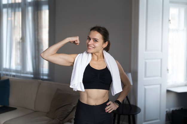Front view of smiley woman showing off her bicep