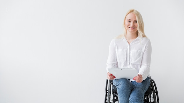 Front view of smiley woman in wheelchair holding tablet
