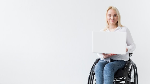 Front view of smiley woman in wheelchair working on laptop