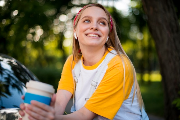 Front view of smiley woman with cup and earbuds