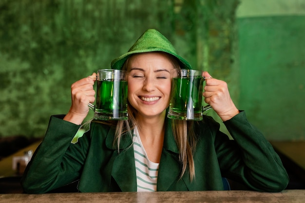 Front view of smiley woman with hat celebrating st. patrick's day at the bar