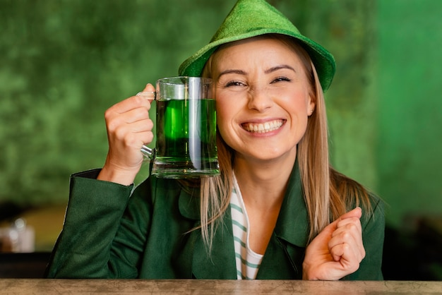 Front view of smiley woman with hat celebrating st. patrick's day with drink
