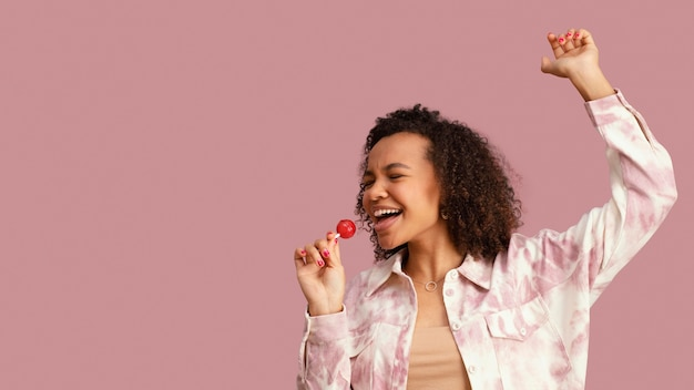 Vista frontale della donna sorridente con lecca-lecca ballando con lo spazio della copia
