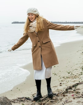 Front view of smiley woman with mittens at the beach during winter