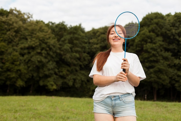 Front view of smiley woman with racket outdoors