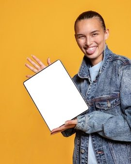 Front view of smiley woman with tongue out holding tablet