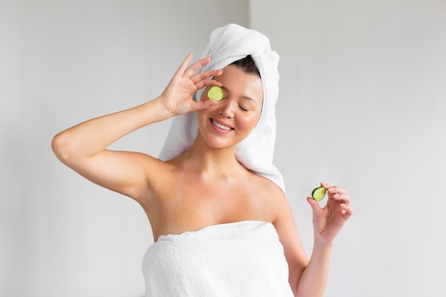 Front view of smiley woman with towel on head holding cucumber slices
