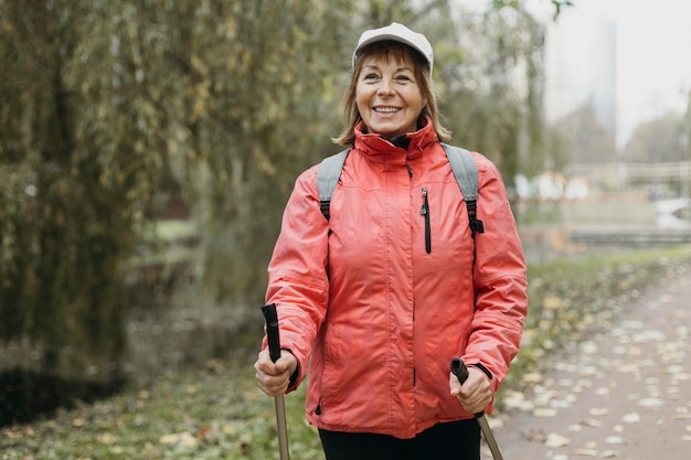 Front view of smiley woman with trekking sticks outdoors