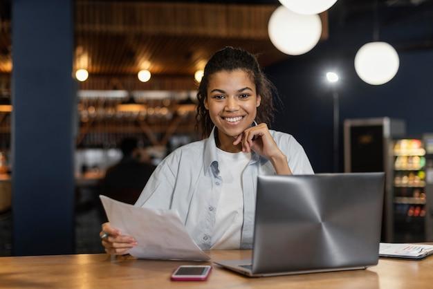 Vista frontale della donna sorridente che lavora in ufficio davanti al computer portatile