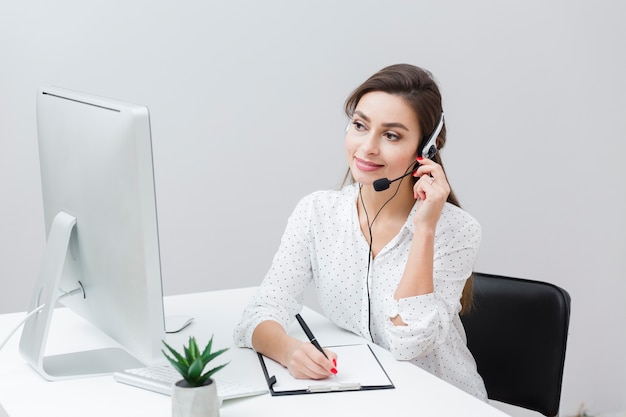 Front view of smiley woman writing something down while talking on headset