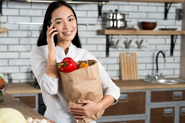 Front view of smiling asian woman talking on mobile phone while holding grocery bag