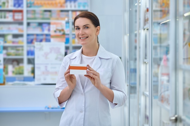 Front view of a smiling attractive female druggist holding a carton box with pharmaceutical drugs