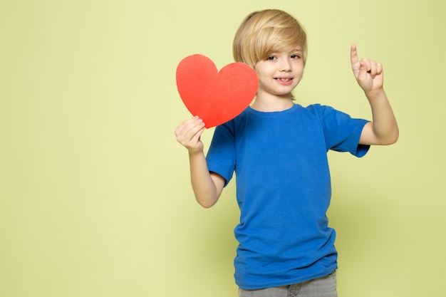 A front view smiling blonde boy holding heart shape in blue t-shirt on the stone colored space