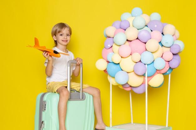 Вид спереди улыбающийся белокурый мальчик, играющий с оранжевым игрушечным самолетом вместе с разноцветными воздушными шариками на желтом столе