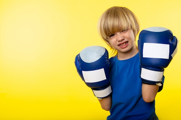 A front view smiling blonde boy posing boxing in blue boxing gloves on the yellow wall