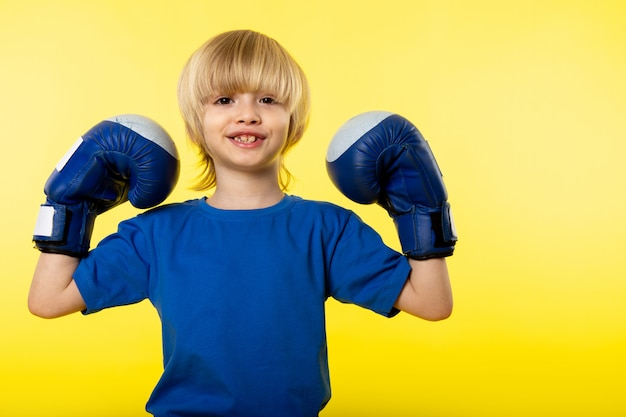 A front view smiling blonde flexing with blue boxing gloves on the yellow wall