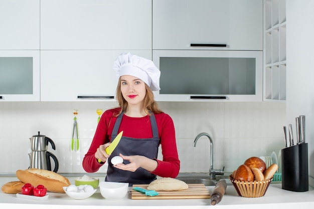 Front view smiling blonde woman in cook hat and apron cracking an egg with knife in the kitchen