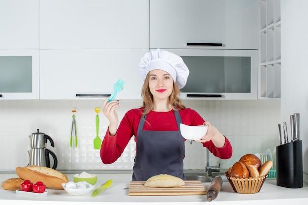 キッチンでブラシとボウルを保持している料理人の帽子とエプロンで金髪の女性の笑顔の正面図