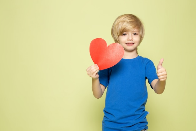 A front view smiling boy in blue t-shirt holding heart shaped figure on the stone colored space