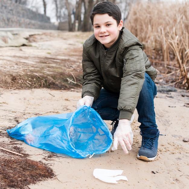 Vista frontale del ragazzo sorridente che pulisce la terra