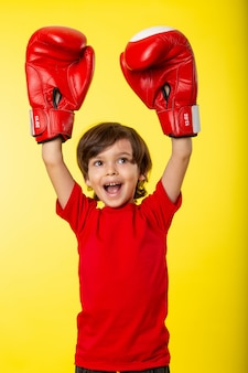 A front view smiling boy in red boxing gloves and without any help