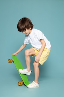A front view smiling boy in white t-shirt riding scateboard on the blue backgorund