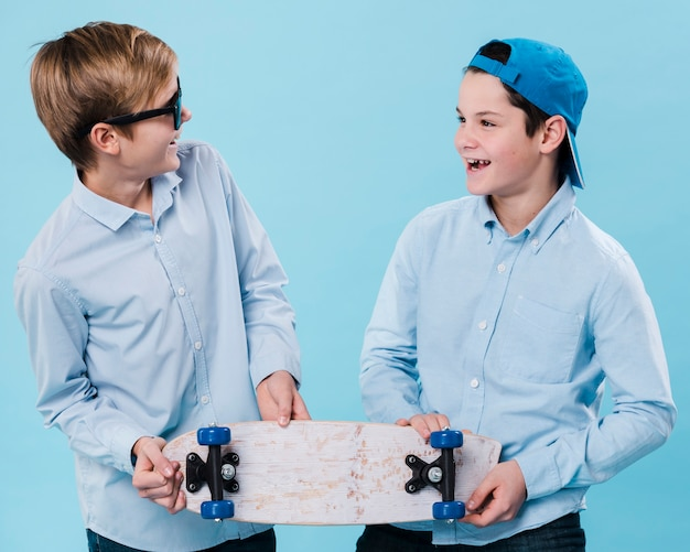 Front view of smiling boys holding a skateboard