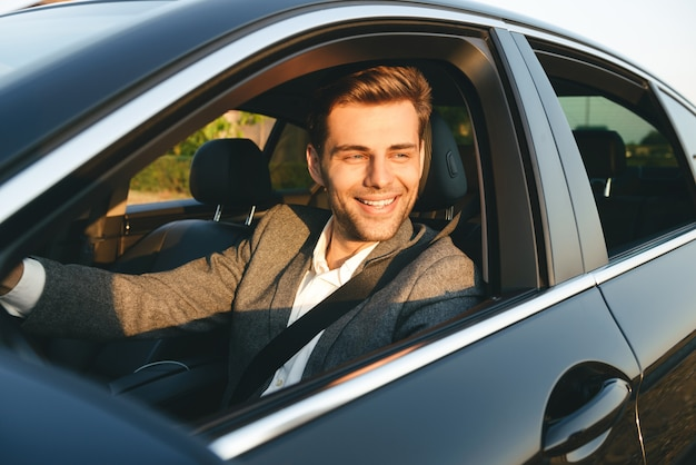 Front view of smiling bussinesman in suit driving